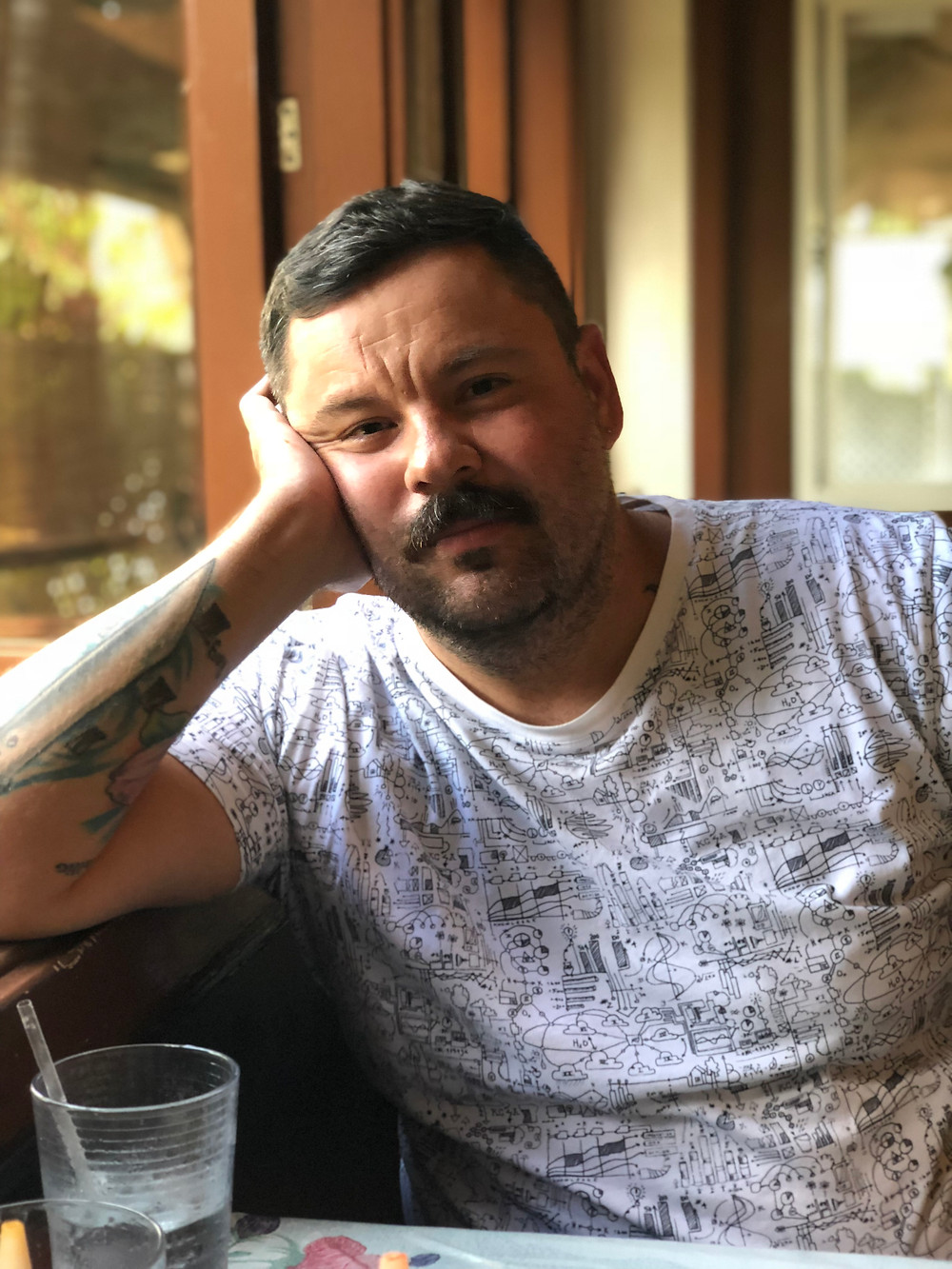 Gustavo Hernandez, a tattooed man with a mustache wears a white t-shirt while sitting at a table. He is leaning with his arm bent on a windowsill and he is resting his face on his hand.