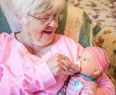 Senior woman holding a baby doll smiling