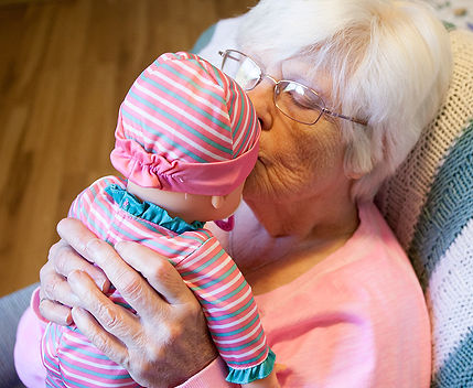 An elderly woman kissing a baby doll.