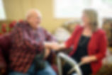 Senior man shaking hands and laughing with a Team Senior advisor in an assisted living facility