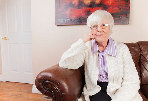 An elderly woman sitting on a leather sofa in an adult foster home