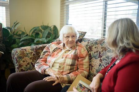 Senior woman sitting on a couch with a Team Senior advisor
