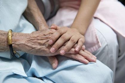 A closeup of a nurses hands holding a seniors hands