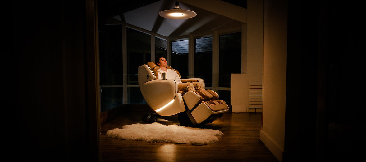 Man relaxing in a white massage chair in a cozy living room