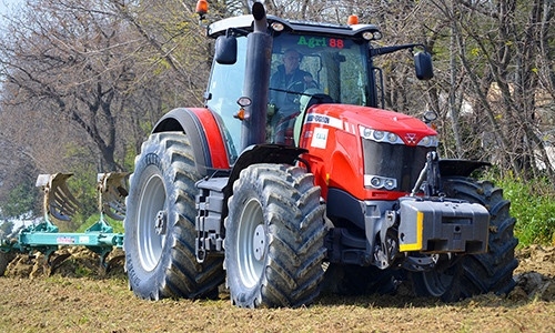 A tractor is plowing farm land with tyres from Leicht's Tyre and Auto