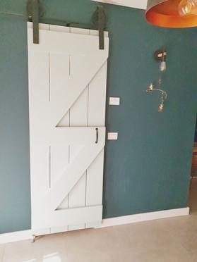 דלת אסם ניגררת צבועה בתכלת בכניסה לחדר הרחצה