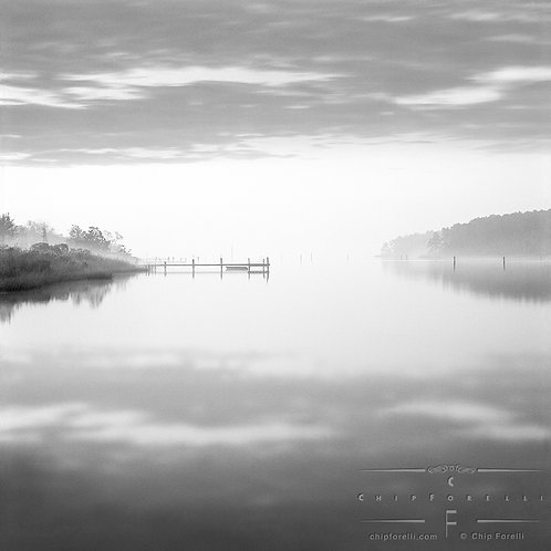 A calm inlet with a boat and dock centered and sky and clouds reflecting in the water in black and white.