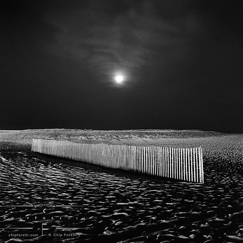 A wooden slat fence in perspective on a moonlit beach with the moon centered in the dark sky in black and white.