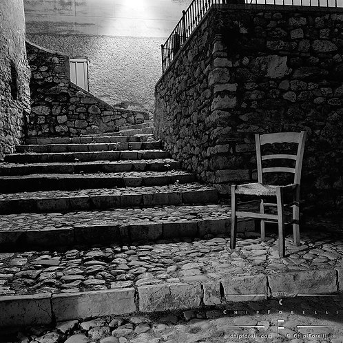 Looking up at wide cobblestone steps in Italy at night with a wooden chair in the foreground in black and white.