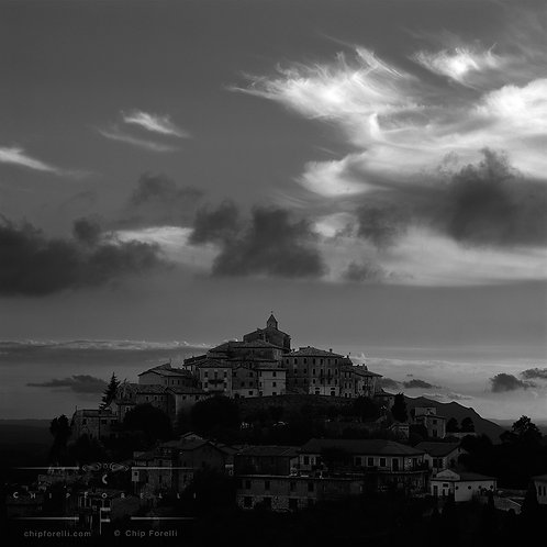 Italian hilltop town in black and white centered and silhouetted against a dawn sky with various sweeping cloud forms.