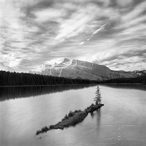An evergreen tree on a tiny island in a lake surrounded by trees and rocky mountains with dramatic clouds filling the sky.