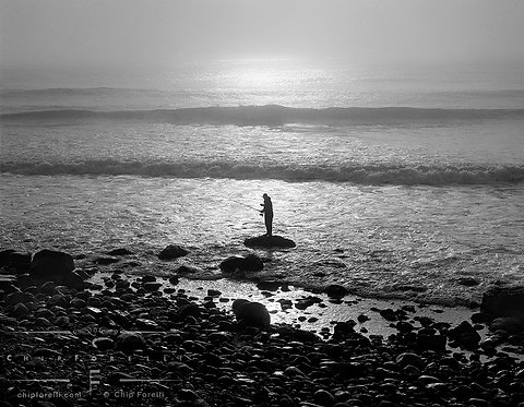 A silhouetted lone fisherman stands on a rock backlit by the sun with breaking waves rolling in.