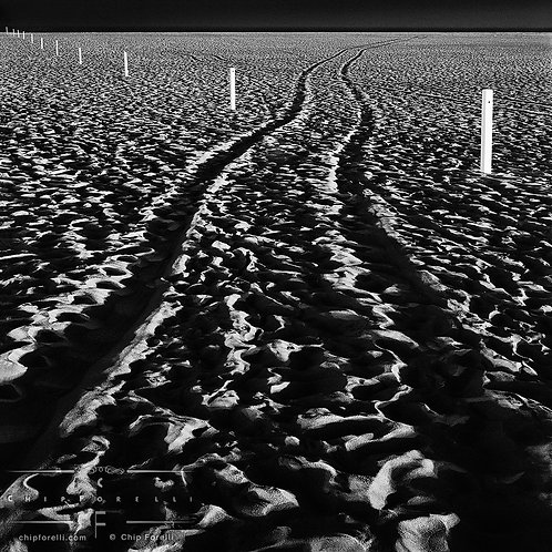 Tire tracks recede into the distance in this night beach photo of footprints with white fenceposts running across the scene.