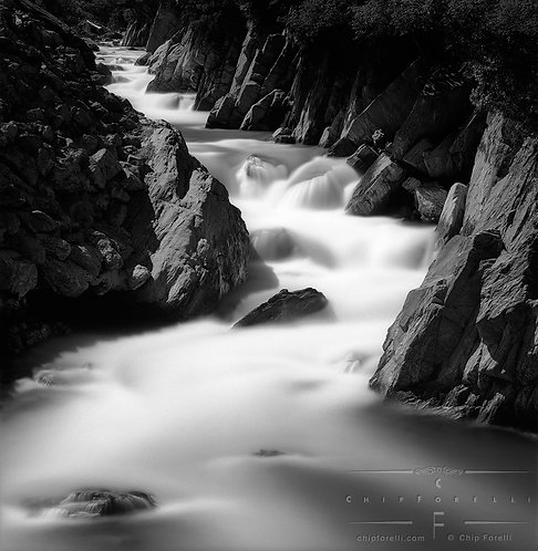 Time exposure of stream in smooth light tones of white and grey rushing between dark rock walls in black and white.