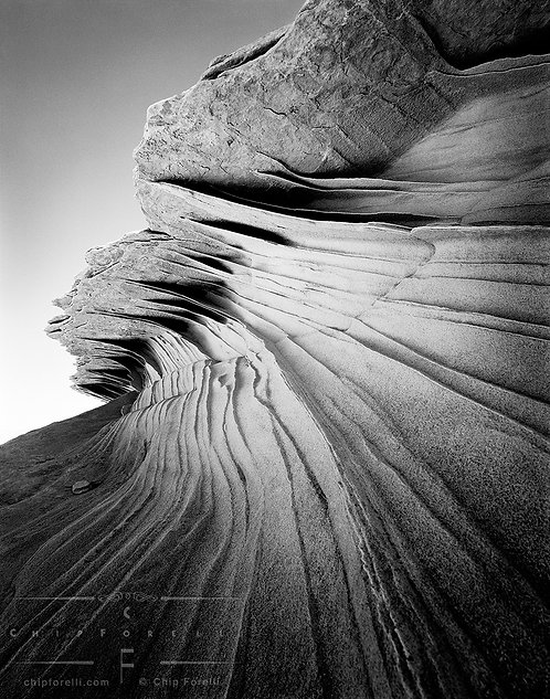 An about to break ocean wave of sandstone in black and white.