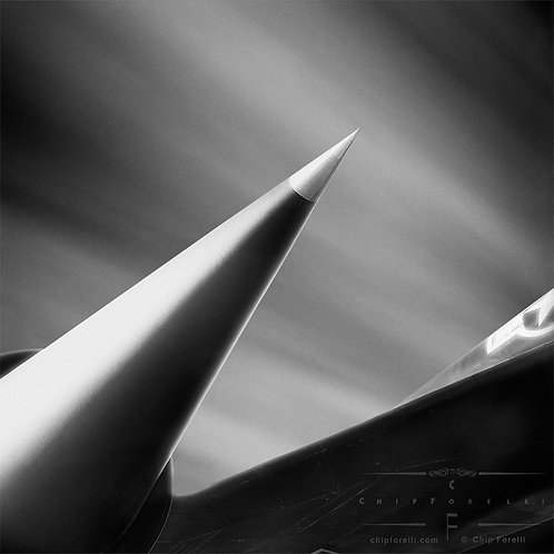 A close up of pointed jet engine intake of Lockheed SR - 71 reconnaissance aircraft with streaking clouds in black and white.