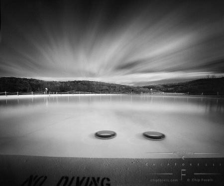 Long exposure of an off season outdoor pool with submerged tires in it with cloud streaked sky in black and white.