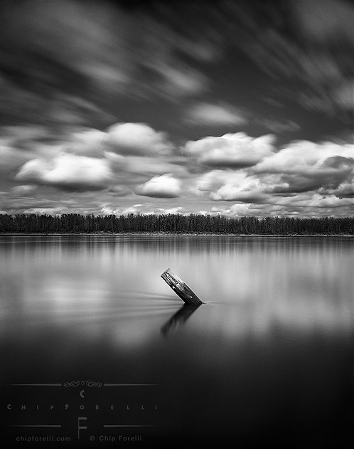 A long exposure of a tilted wooden piling in a river with dramatic cumulus clouds moving overhead in black and white.