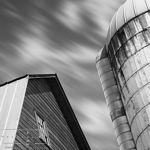 A time exposure showing a portion of a barn and silo with clouds streaking overhead in black and white.
