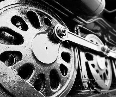 A close up of locomotive drive wheels in perspective in black and white.