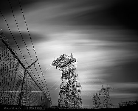 Long exposure of electrical stanchions and barbed wire fence with a cloud streaked sky in black and white.