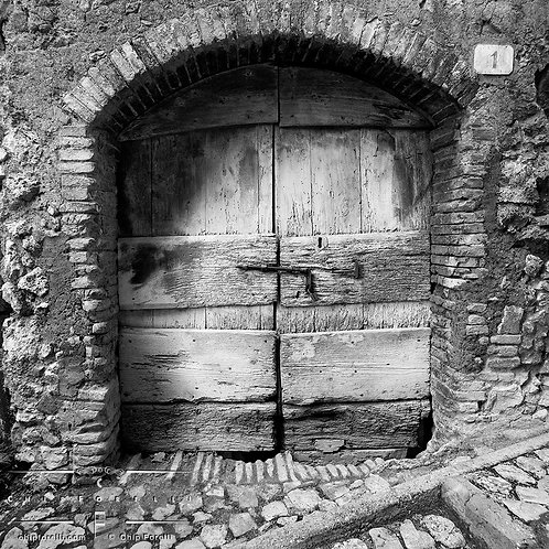 Arched ancient wooden doors in Italy encased in a deteriorating stone wall on a cobblestone street.