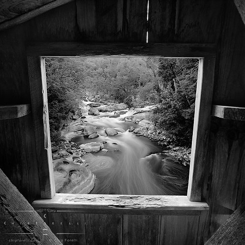 Black and white view through the window of a covered bridge looking at a stream running through the natural landscape.