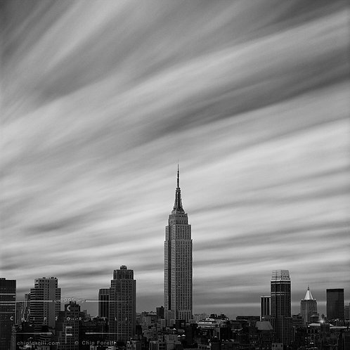 A distant view in black and white of the Empire State Building isolated against an immense sky of clouds in motion.