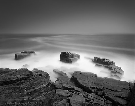 A long exposure of a rocky ocean shoreline contrasting with smoothed out patterns on the surface of the water.