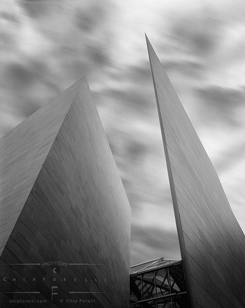 The pointed concrete modern architectural forms of the National Gallery of Art against up into a cloud streaked sky in B&W.
