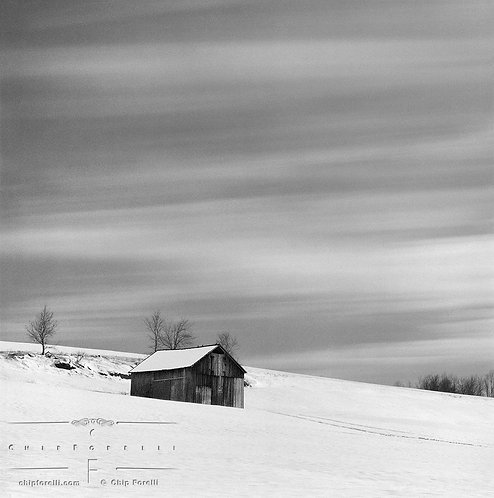 A time exposure of a rural winter landscape in black and white with a barn in a snowy field and streaking clouds overhead.