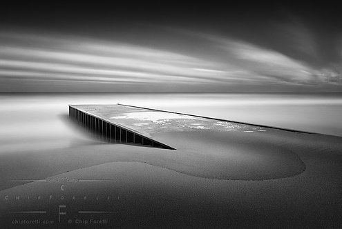 A steel pier in a surreal dreamy seascape of streaking clouds across the sky and smoothed out wave action in black and white.