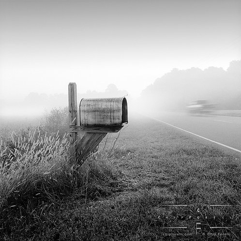 A rural mailbox at the side of a foggy road in perspective with a vehicle in motion speeding by in black and white.