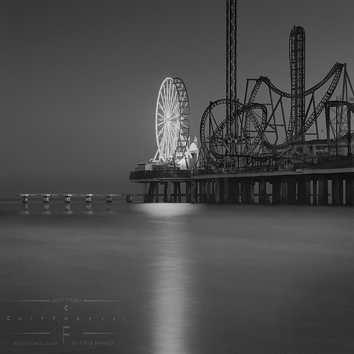 A silhouetted amusement park on a dark pier at night with a ferris wheel lit up reflecting in the water.