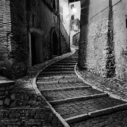 Cobblestone steps in Italy at night twisting between stone walls with an old style streetlight illuminating the scene in B&W.
