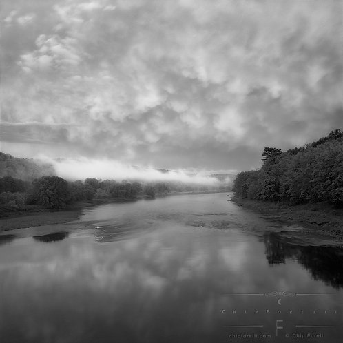 Looking down a river from a bridge with a sky dense with various cloud forms and ground fog in the distance.