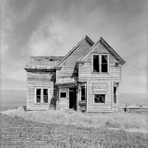 In this photograph of an abandoned run down wooden house in the middle of a plain in black and white.