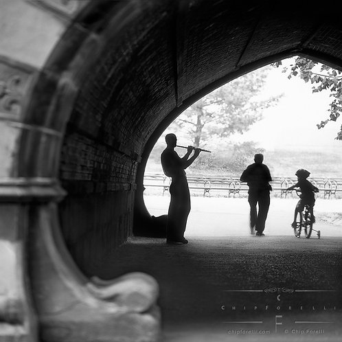 A silhouetted street musician playing the flute under an overpass with silhouetted figures walking by in black and white.