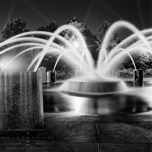 A circular fountain at night shooting plumes of water with spotlights in the background sky in black and white.