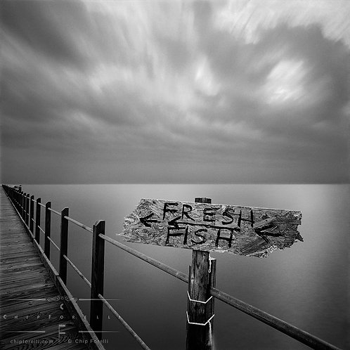 A time exposure of a pier with a homemade sign and body of water with a silky sheen and cloud streaked sky in the background.