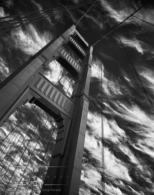 A perspective view from the bottom of a tower on the Golden Gate Bridge with streaked clouds against a dark sky.
