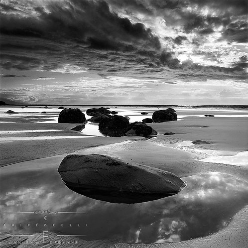 At low tide a rock on a broad beach is embedded in a reflective tidepool with dramatic backlit clouds overhead.