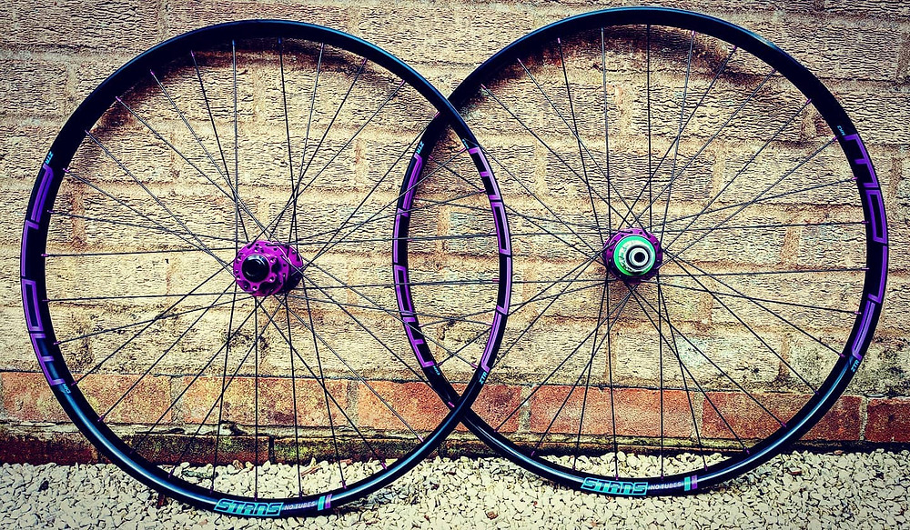 Custom hand built mountain bike wheels Stans Flow MK3 laced to purple Hope Pro 4 hubs