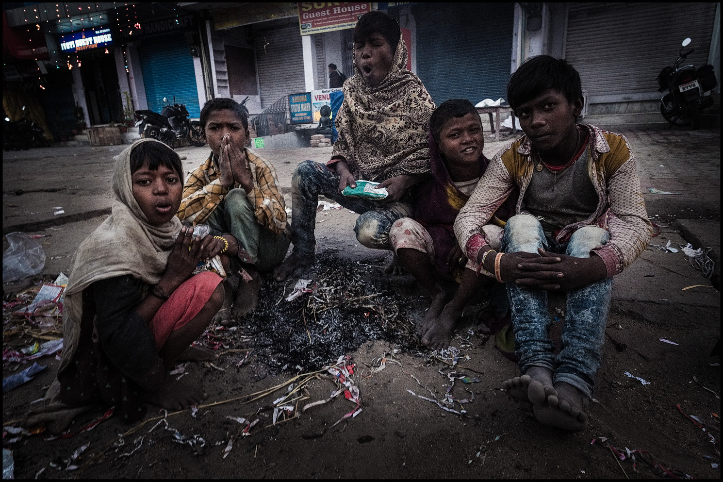 Street Kids Keeping Warm Before Dawn, Bodhgaya, India  India is nothing if not a paradox. Bodhgaya, a UNESCO site renown because it is where the Buddha purportedly attained Enlightenment, is visited by tens of thousands each day. But there is crushing poverty. So widespread, the issues of class, geography, race so complex, the mind can become numb after days and weeks there. To counter this, when on assignment or with personal work, I photograph people just before daybreak and at dusk. Then, it seems a veil dissolves. Cultural differences dissolve. The heart, mine and theirs, is less protected. Each day I'd awake an hour or two before dawn to shoot. Most mornings, these boys would have collected scraps of cardboard, to make a fire, a modest respite from the bone chilling cold of a north Indian night.