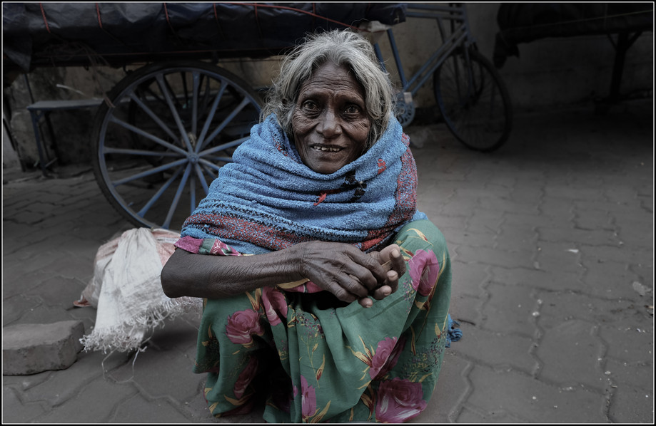 The Streets of Bodhgaya  My photographic work in the U.S., commercial and personal, has mostly been of wilderness. After decades of shooting, however, the line blurs (no pun intended) between landscape work and portraiture. Landscapes are the portraits of place - mountains, rivers, chasms; light and shadow the wrinkles, the age and laugh lines, the lesions of suffering of the earth as it's features emerge and collapse, and struggle against the impact of we humans. In Asia, I mostly shoot portraiture. It's obvious why. In each face the landscape of lineage, culture, class; joy, and often, incalculable suffering. This woman and I squatted together in silence for ten minutes or so, until my knees couldn't any longer. She didn't speak, but for her extraordinary eyes. I used a lens that required me to be very close - a foot or so away. It required of me both vulnerability and candor. This seemed the only honorable way to convey something of her life.