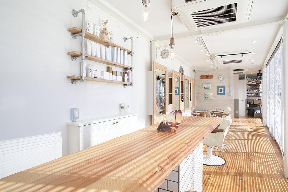 サーフスタイルの美容室。受付カウンターは杉の一枚板。