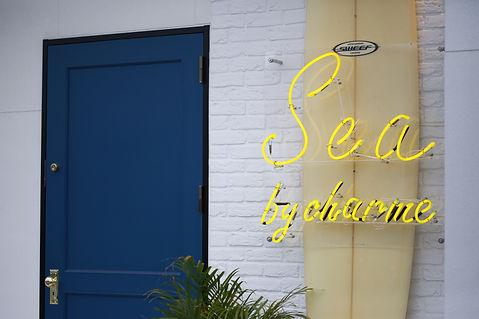 白の外観にサーフボードと黄色のネオンサイン