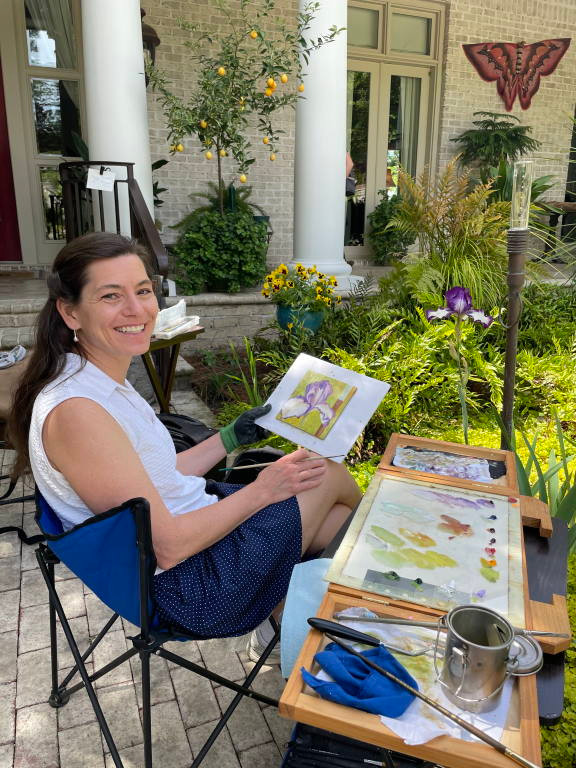Photo of Barbara Teusink doing plein air painting in garden