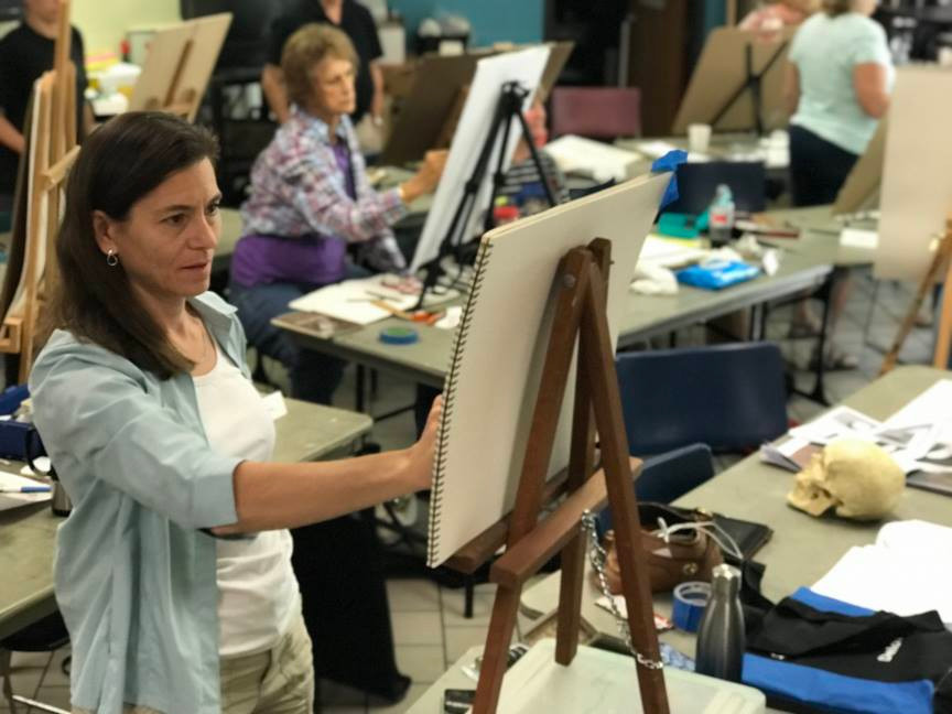 Barbara Teusink standing at her easel to paint