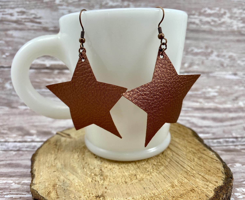 Copper faux leather star earrings.